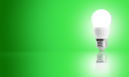 e27: Glowing LED energy saving bulb on a green background Stock Photo