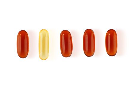 A single yellow pill in a row of orange pills, a concept of individuality and diversity. Isolated on a white background. Stock Photo
