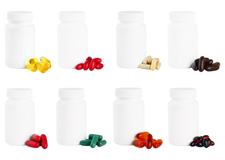 A set of capsules next to a white plastic medicine bottle. Isolated on white background.