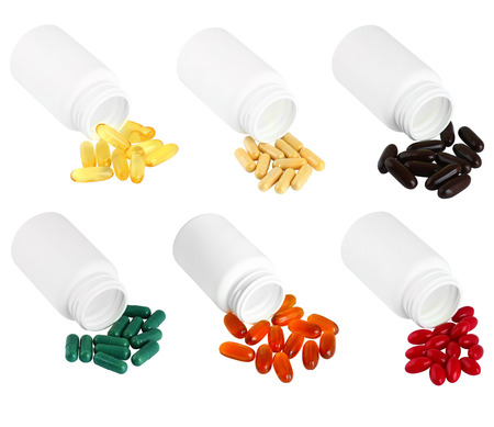 A set of pills spilling out of white plastic medicine bottle. Isolated on a white background. Stock Photo