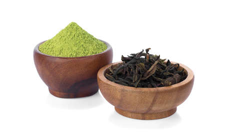 Green tea powder with dried green tea leaves in wooden bowl isolated on white background