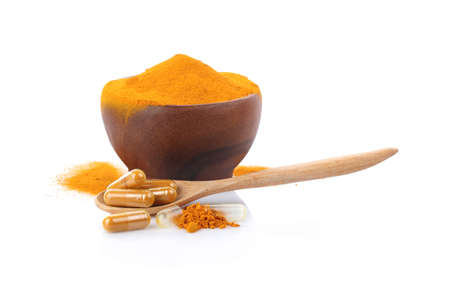 Turmeric , turmeric powder in wooden cup with wooden spoon and turmeric capsules on white background.