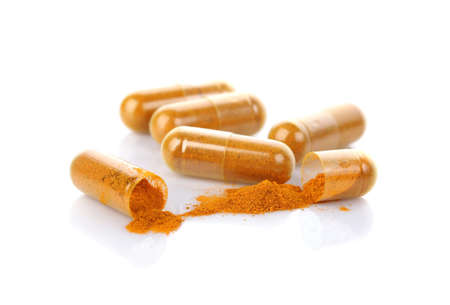 Turmeric capsules isolated on white.