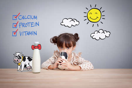 Adorable baby girl holding glass of milk and dringking milk