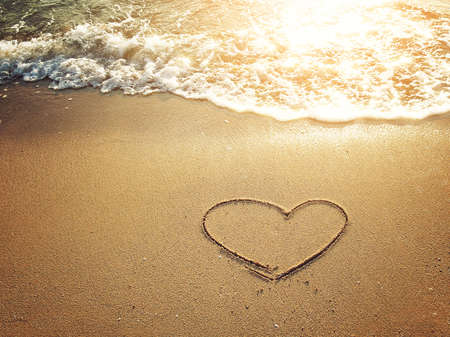 evoking: Hearts drawn on the sand of a beach