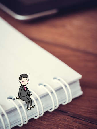 Happy businessman concept : Tiny cartoon man sit on note book in suit having break with smiley face