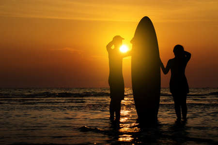 island: Man and girl with surfboard on the beach at sunset