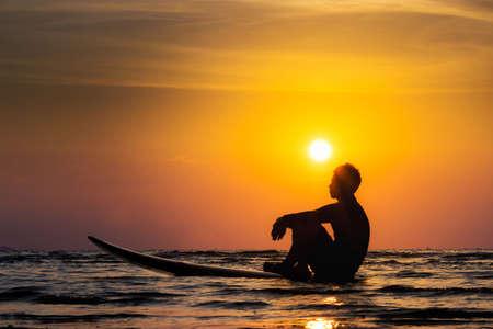 Silhouet van surf man zit op een surfplank. Surfen bij zonsondergang strand. Outdoor watersport avontuur lifestyle. Zomeractiviteit. Het knappe mannelijke model van Azië in zijn jaren '20.