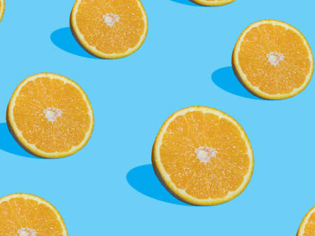 Fresh orange slices on blue background with shadow , top view, flat lay, close up , pattern. Summer and healthy citrus fruit concept