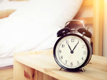 Closeup retro alarm clock on Bedside table with bed background and copy space, retro style