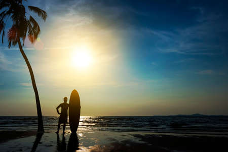 Silhouette of surf man stand with a surfboard and coconut palm. Surfing at sunset beach. Outdoor water sport adventure lifestyle.Summer activity. Handsome Asia male model in his 20s.