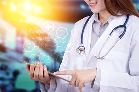 Healthy technology concept : Young Asian woman doctor using technology on tablet for patient chart with hologram graphic chart popup from tablet on doctor hand for patient consultants,  anonymous face