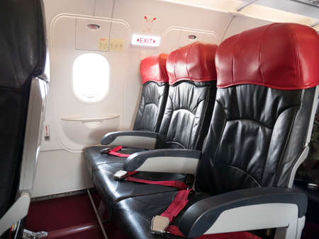 Airplane flight safety concept : emergency exit seat row in airplane , exit sign light over plane emergency exit door turn on for passenger.