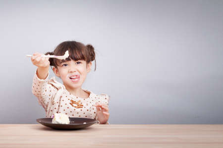 Kids enjoy eating concept : Happy little cute mixed race girl enjoy eating cake with smiley face , tongue stick with spoon in her hand for invite to eat. Kid poster background.