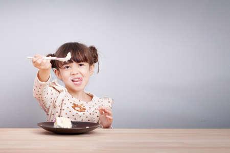 Les enfants apprécient le concept de manger: Bonne petite fille mignonne mélangée de race aiment manger le gâteau avec le visage souriant, bâton de langue avec la cuillère dans sa main pour inviter à manger. Arrière-plan d'affiche enfant. Banque d'images