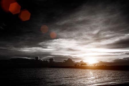 coucher de soleil sur un ciel nuageux à la plage de la mer avec la silhouette pont de roche et de l'arrière-plan de l'arbre, la couleur noir et blanc avec effet de lumière rouge lens flare