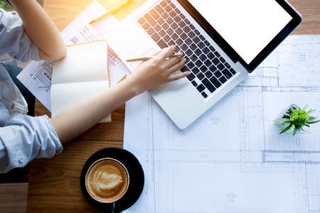 architect , engineering , creative and designer workspace concept : Top view of Asian female architect working with blueprint , notebook and laptop on architectural project , anonymous face. Banque d'images