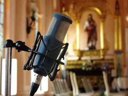 Schließen Sie oben vom Retro- Weinlesemikrofon gegen mit Unschärfehintergrund in der Kirche