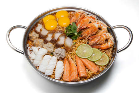 Pot of spicy instant noodles isolated on white background. Topping with eggs, lemon, pork , crispy pork, sausage , shrimp, squid, crab and coriander