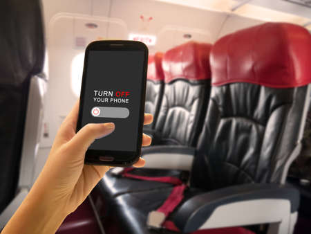 In-flight Security concept. Passenger turn off portable electronic devices and mobile phone or use flight mode on airplane aboard airliners between flight service