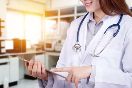 Doctor in hospital working with modern technology for healthy. close up of friendly doctor with smile pointing at tablet for patient data chart with hospital laboratory blur background