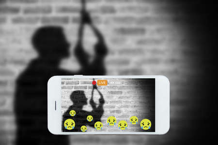 livestream: Problem of using social networks with wrong purpose effect concept:silhouette of sad man hanging suicide stream his commits suicide stream live on social media. Crime ,violence within social networks. Stock Photo