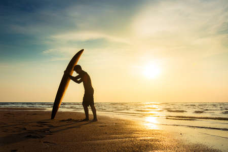 Surfing for water sport outdoor activity lifestyle concept. Silhouette of young happy surf man at white beach with surfboard. Surfer on the beach in sea shore at sunset time with beautiful light. Stock Photo