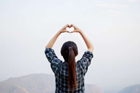 I love travel concept : Freedom traveler woman standing with heart shaped hands and enjoy a wonderful nature Imagens