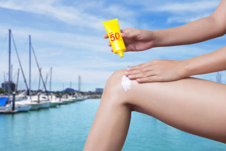 woman applying sunscreen on her leg with blur boats docked at the yacht club background. SPF sunblock protection concept. Travel vacation