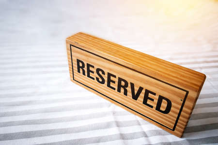 reserved table. reserved wooden sign on table for reservation placed. reserved table in the restaurant.  Archivio Fotografico
