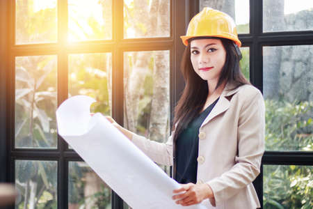 portrait of beautiful Asian woman architect builder with yellow helmet hard hat studying blueprint plan of the rooms, serious civil engineer working with documents on construction site Standard-Bild