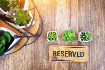 reserved sign on top of a wooden table in a restaurant, reservation seat at restaurant for dating on celebrate day concept, restaurant with reserved on table decorate with small cactus