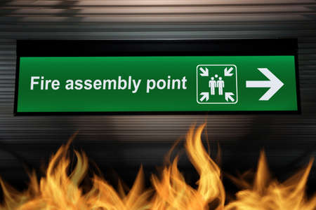 green fire assembly point sign hanging from ceiling with fire flames are burning on the ground below. security based quality awareness concept