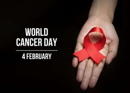 4 February , World Cancer Day with ribbon on human hand for campaign poster about cancer Stock Photo