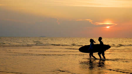 silhouette of young happy people ,surf man and girl running with long surf boards at sunset tropical beach. surfer on the beach in sea shore at sunset time with beautiful light. water sport activity
