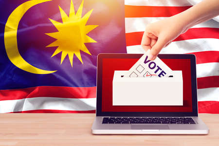 online vote , poll, exit poll for Malaysia general election concept. close up hand of a person casting a ballot at elections during voting on canvas Malaysia flag background.