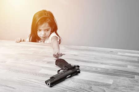 seguridad y accidente en el concepto de hogar. los niños intentan jugar el arma de los padres en la mesa. color monótono Foto de archivo