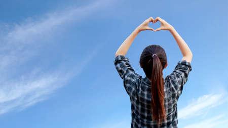 Frau hebt ihre Hände, um Herzform in der Luft mit blauem Himmel im Hintergrund zu machen