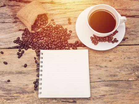 hot coffee cup with coffee bean and notebook on wooden table. coffee background menu for cafe or coffee shop Stock fotó