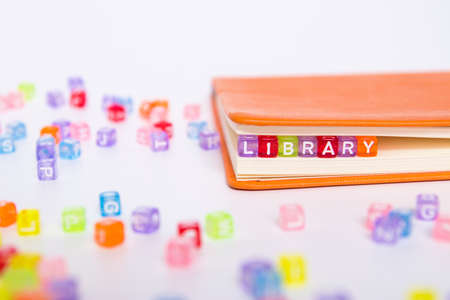 LIBRARY word on colorful bead block as bookmark in book. knowledge from book resource in library concept