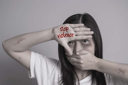 stop violence against women campaign. Asia woman with bruise on arms and face use one hand close mouth and the other hand write the word stop violence.