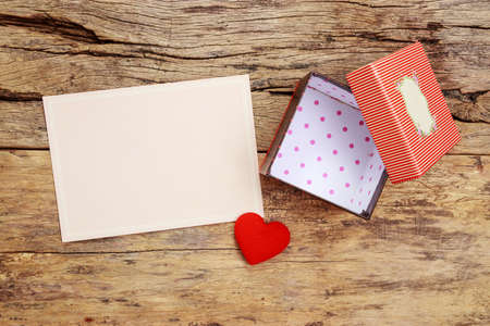 blank pink greeting card with border frame and empty red present gift box with open cover, decorate with red heart on wooden background
