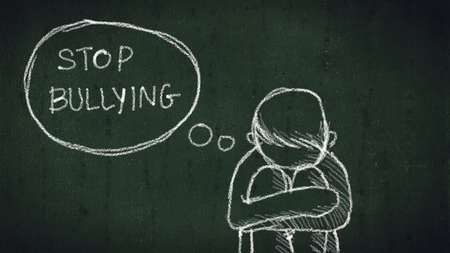 sad young boy sitting on the floor with text stop bullying written with chalk on chalkboard. social problems of humanity Stock Photo