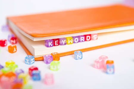 KEYWORDS word on colorful bead block as bookmark in book. keywords research and content marketing idea concept Stok Fotoğraf