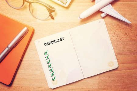 Reise-Checklisten-Konzept. Notizbuch mit leerer Checkliste auf Holzuntergrund mit Brille und Flugzeugmodell
