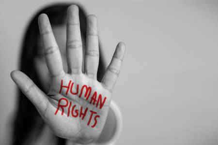 human rights concept. woman raised her hand for dissuade, hand write the word human rights in red color.