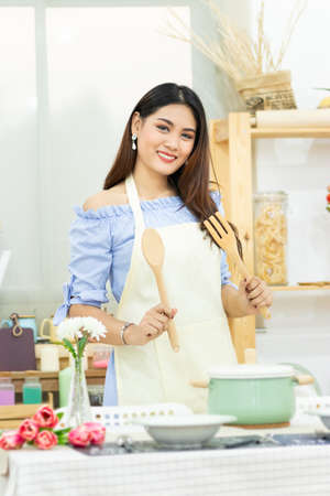 beautiful Asian woman holding wooden cutlery behind dining table with pot , dish and kitchenware in the kitchen room with smiley face 免版税图像