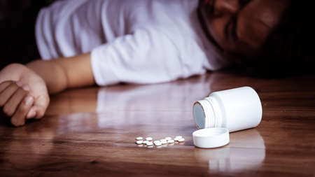 depression man committing suicide by overdosing on medication. close up of overdose pills from plastic medicine container with depress man on the floor Stock Photo