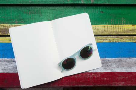 open blank white page book on colorful wooden background , decoration with sunglass fashion