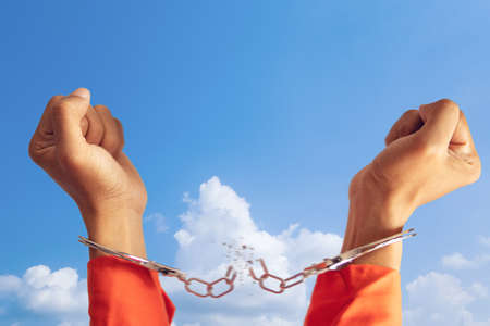 freedom concept. two hands of prisoner with broken handcuff for freedom meaning with blue sky at background